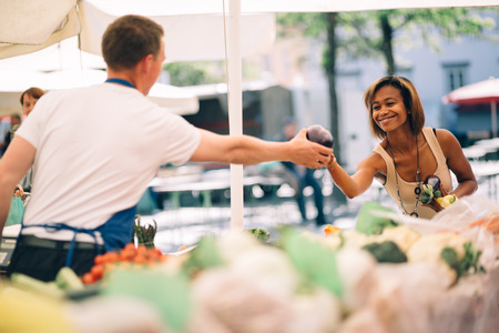 Photo for Young woman buying vegetables at farmers market - Royalty Free Image
