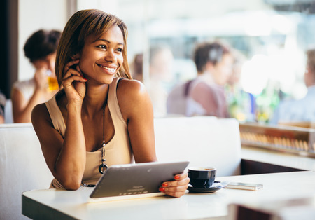 Photo for Young woman using tablet computer in coffee shop - Royalty Free Image