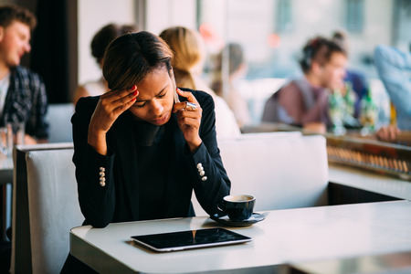 Photo for Stressed young businesswoman talking on the phone in coffee shop - Royalty Free Image