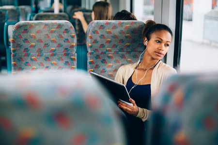 Photo for Young woman listening to music on train using tablet computer - Royalty Free Image