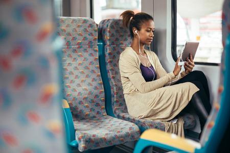 Photo pour Young black woman listening to music on train using tablet computer - image libre de droit