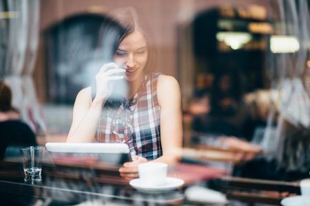 Photo pour Young woman talking on the phone in coffee shop - image libre de droit