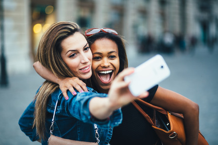 Foto de Multi ethnic Friends having fun in city taking selfie - Imagen libre de derechos