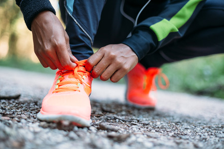 Photo pour Young woman tying laces of running shoes before training - image libre de droit