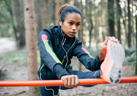 Photo for Young female runner stretching in the woods - Royalty Free Image