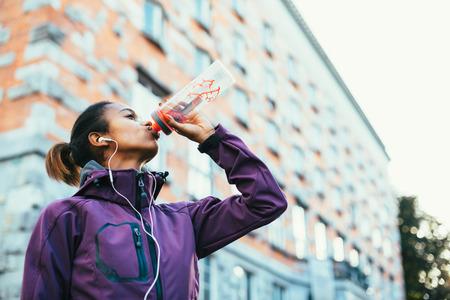 Foto für Young woman drinking water after running in city - Lizenzfreies Bild