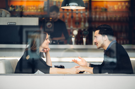 Photo pour Couple in love drinking coffee laughing in coffee shop - image libre de droit