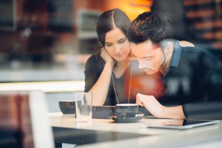 Photo pour Couple using tablet computer in coffee shop - image libre de droit