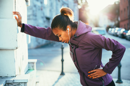 Photo pour Tired young woman cathing her breath after a long run - image libre de droit