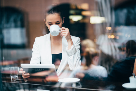 Photo for Young businesswoman drinking coffee and using tablet computer in cafe - Royalty Free Image