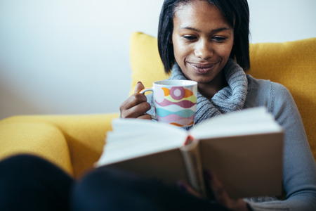 Photo pour Woman drinking tea and reading book on couch - image libre de droit