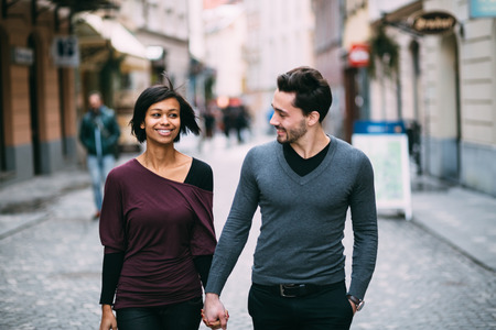 Foto de Interracial couple holding hands on the street - Imagen libre de derechos