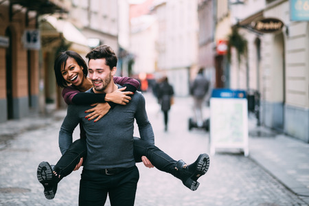 Photo for Young man giving girlfirend piggyback ride - Royalty Free Image