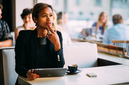 Photo pour Pensive black businesswoman using tablet computer in coffee shop - image libre de droit