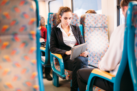 Photo pour Young millennial businesswoman traveling train bus tablet computer - image libre de droit