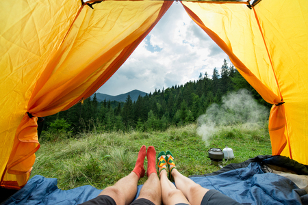 Photo pour legs of a couples of man and woman in a tent outdoors - image libre de droit