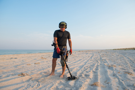 Photo for Man with a metal detector on a sea sandy beach - Royalty Free Image