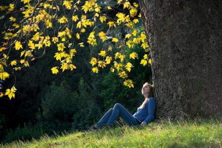 Foto de Girl sitting on the grass under a maple tree in autumn - Imagen libre de derechos