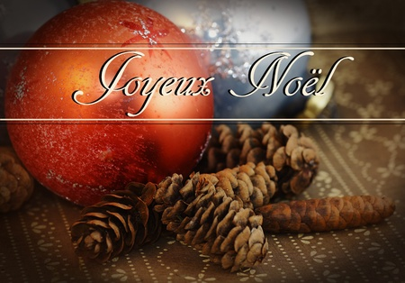 Grungy holiday theme: Joyeux Noel text over old vintage glass Christmas ornament on dark brown wallpaper with pine cones.