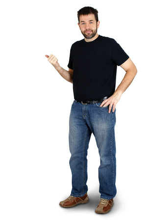 Photo pour Complete body of ordinary guy or man pointing besie him and smiling, copy space  - image libre de droit