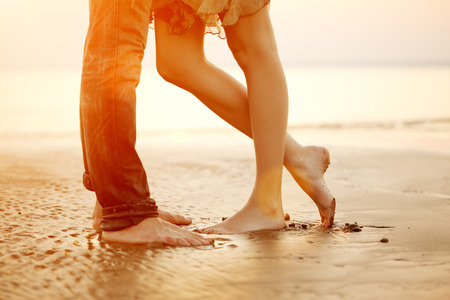 Foto de A young  loving  couple hugging and kissing on the beach at sunset. Two lovers, man and woman barefoot near the water. Summer in love  - Imagen libre de derechos