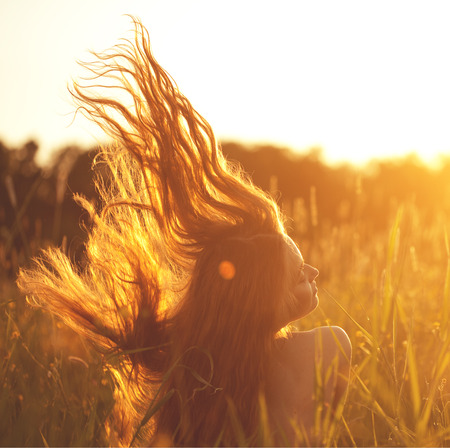 Photo for Beautiful smiling woman in a field at sunset. Trendy young girl at sunset with flying hair - Royalty Free Image