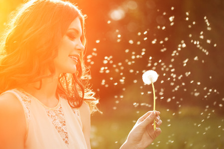 Foto de Young spring fashion woman blowing dandelion in spring garden. Springtime. Trendy girl at sunset in spring landscape background. Allergic to pollen of flowers. Spring allergy - Imagen libre de derechos