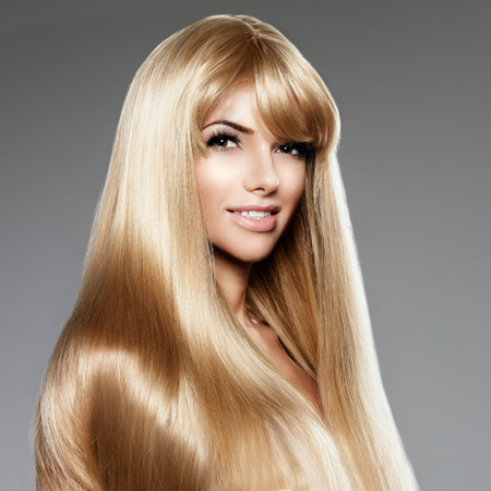 Beauty young woman with luxurious long blond hair. Haircut with fringe. Girl with fresh healthy skin, prifessional makeup, red lips, long eyelashes and manicured nails shiny. Fashion model in spa hair care salon.  Girly sexy trendy hairstyle look.