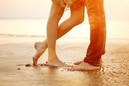 Foto per A young  loving  couple hugging and kissing on the beach at sunset. Two lovers, man and woman barefoot near the water. Summer in love - Immagine Royalty Free
