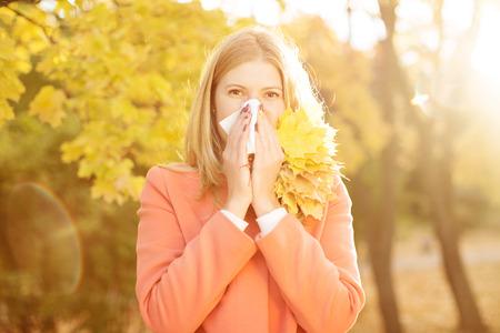 Foto de Girl with cold rhinitis on autumn background. Fall flu season. - Imagen libre de derechos