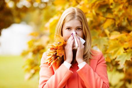 Foto de Girl with cold rhinitis on autumn background.  - Imagen libre de derechos