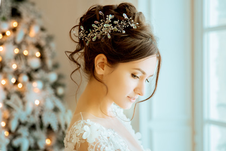 Photo pour Bride. Wedding. The bride in a short dress with lace in the crown earrings. Wedding bouquet, makeup, hairstyle. Wedding Style - image libre de droit