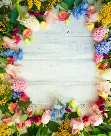Foto de Spring flowers on wood background. Summer blooming border on a wooden table. - Imagen libre de derechos
