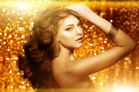 Photo for Golden beautiful fashion woman, model with shiny  healthy long volume hair. Waves curls updo volume hairstyle. Hair Salon.Girl with luxurious haircut on  gold background - Royalty Free Image