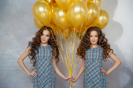 Photo for Girls twins sisters with updo hair at a partyon the background of golden balloons and stars. Women at the birthday party - Royalty Free Image