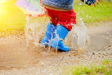 Photo for Child jumps on puddles in boots. Baby in the rain. A boy with a rainbow umbrella is walking outside. Autumn, vacation - Royalty Free Image
