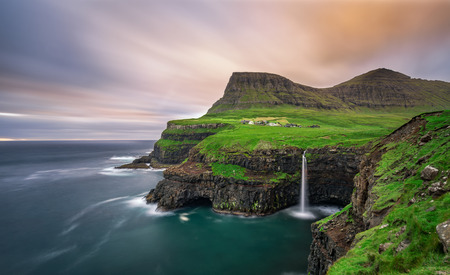 Foto de Gasadalur village and its iconic waterfall, Vagar, Faroe Islands, Denmark. Long exposure. - Imagen libre de derechos