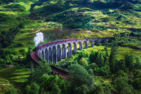 Photo pour Glenfinnan Railway Viaduct in Scotland with the Jacobite steam train passing over. Artistic vintage style processing. - image libre de droit