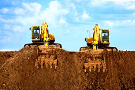 Foto de Two excavators dig the ground at the construction site - Imagen libre de derechos
