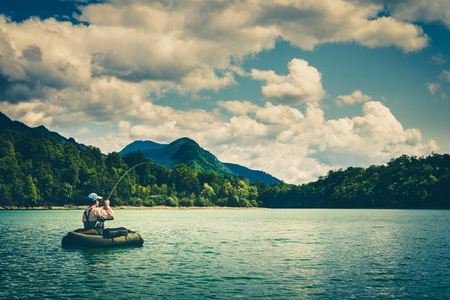 Foto de Fisherman sitting in bellyboat and fighting with big trout on lake in Jesenice, Slovenia. Still water fly fishing and outdoor lifestyle theme. Moody, contrasty, toned and faded look. - Imagen libre de derechos