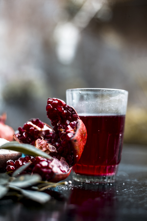Photo for Herbal and organic face pack of pomegranate with some ground or powdered oats to revitalize skin on wooden surface with pomegranate seed juice and some rose petals and leaves. - Royalty Free Image