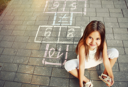 Photo pour beautiful cheerful little girl playing hopscotch on playground outside - image libre de droit