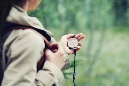 Photo for young woman discovering nature in the forest with compass in hand, travel lifestyle concept - Royalty Free Image