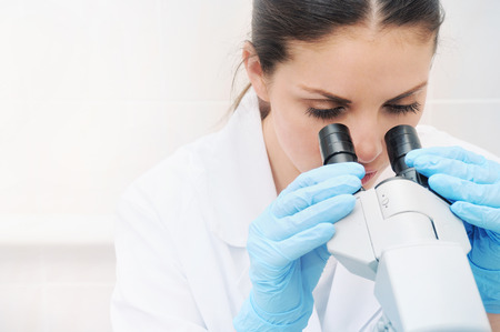 Foto de young woman medical researcher looking through microscope in laboratory medicine concept - Imagen libre de derechos