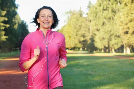 Foto de Portrait of elderly woman running with headphones in the park in early morning. Attractive looking mature woman keeping fit and healthy. - Imagen libre de derechos