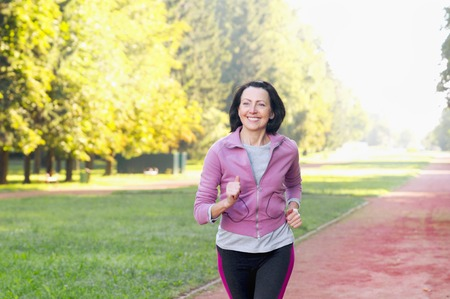 Foto de Portrait of elderly woman running in the park in early morning. Attractive looking mature woman keeping fit and healthy. - Imagen libre de derechos