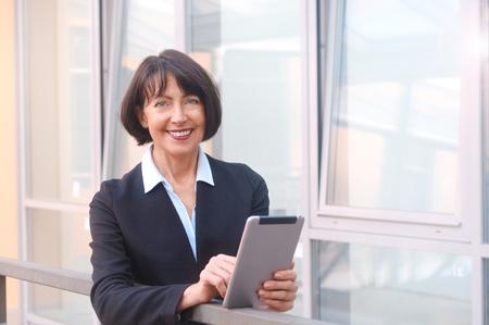 Foto de Mature businesswoman uses wireless tablet, outdoors background. Positive facial expressions. Work anywhere concept. - Imagen libre de derechos