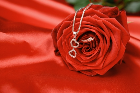 Photo for Valentine's day necklace with two hearts pendant and a ring on red rose. - Royalty Free Image