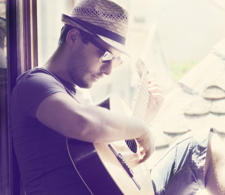 Photo for Young man sitting on the window playing the guitar - Royalty Free Image