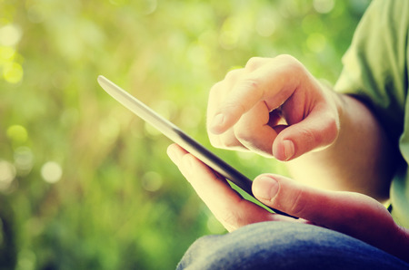 Foto de Man holding tablet in the park - Imagen libre de derechos